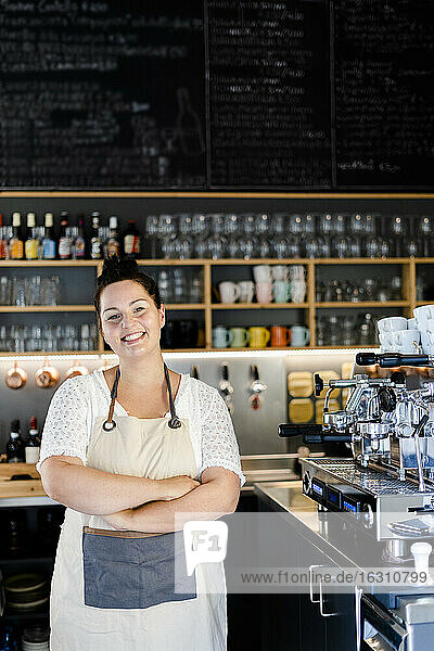 Smiling female entrepreneur with arms crossed standing in cafe