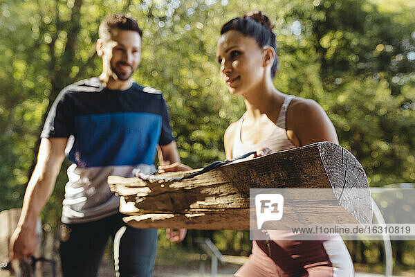 Woman and man lifting up heavy logs on a fitness trail
