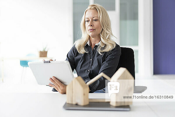 Businesswoman with model on desk using digital tablet in home office