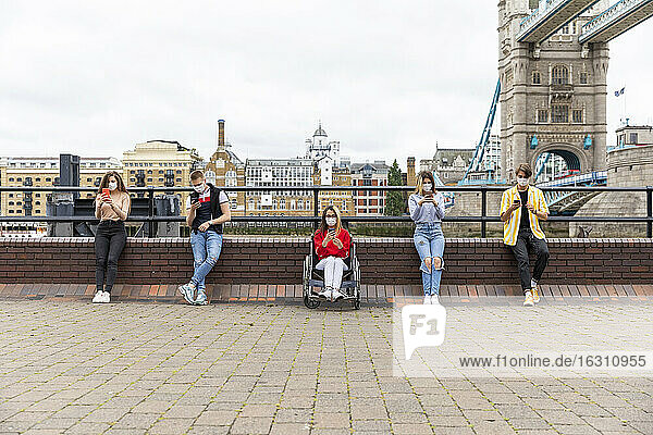 Friends maintaining safe distance and using mobile phones with Tower Bridge in background  London  UK