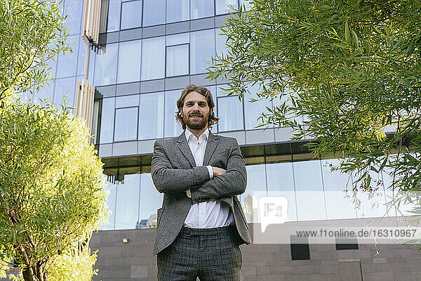 Confident male entrepreneur standing with arms crossed against office building