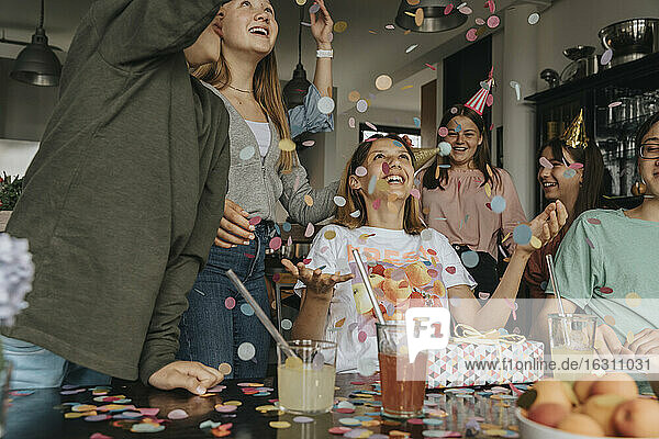Friends throwing confetti on cheerful teenage girl in birthday party at home