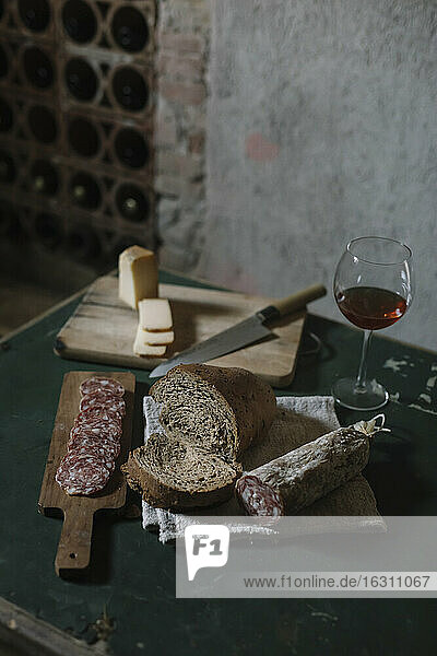 Fresh salami sausage with homemade bread and wine on table in cellar