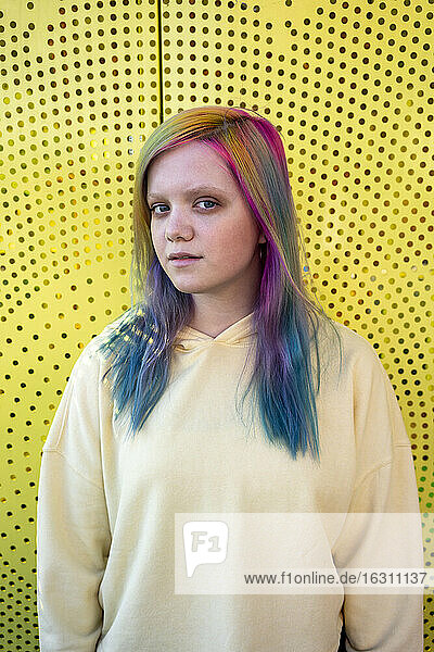 Portrait of young woman with dyed hair in front of yellow wall