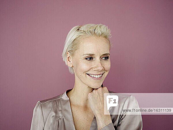 Close-up of smiling businesswoman looking away against purple background