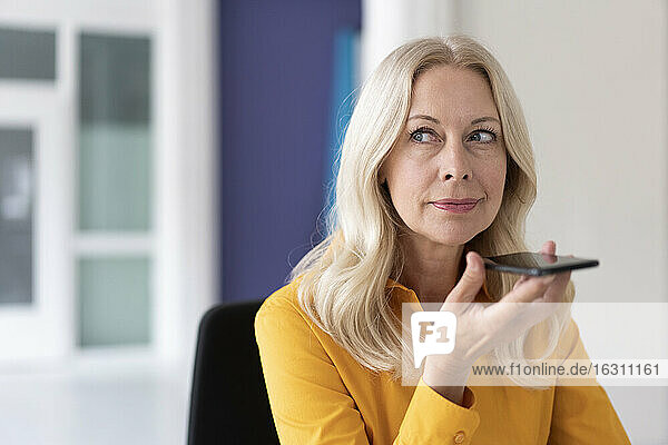 Close-up of businesswoman talking over mobile phone while sitting in home office