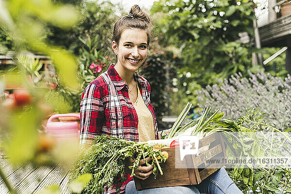 Smiling beautiful woman with vegetable crate sitting in community garden