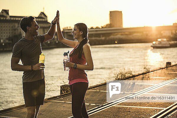Smiling friends with water bottle giving high-five at harbor
