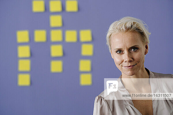 Smiling businesswoman with adhesive notes stuck on blue wall in office
