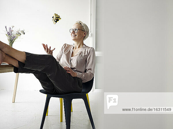 Smiling businesswoman playing with Rubik's cube while relaxing at desk in loft office