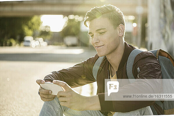 Smiling handsome man using smart phone while sitting on street during sunny day