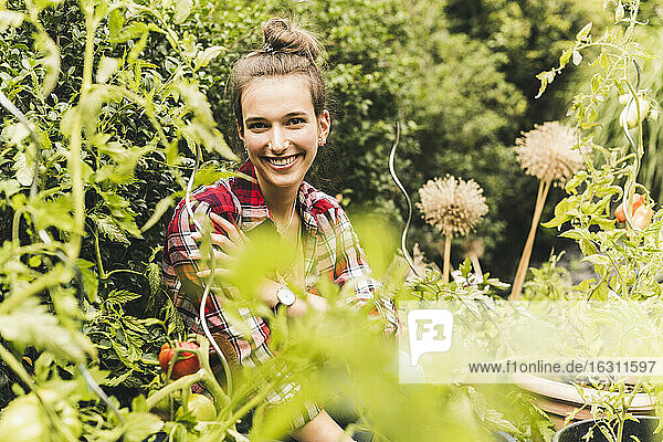 Smiling beautiful woman sitting amidst plants in vegetable garden