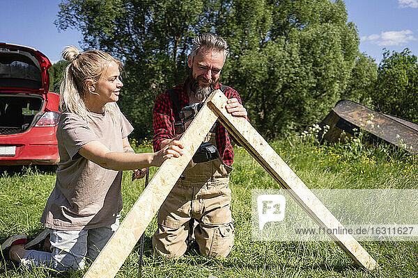 Beautiful woman helping carpenter and building playhouse on grass during sunny day