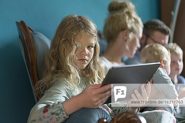 Girl holding digital tablet while sitting with family in living room at home