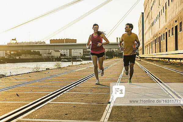 Smiling male and female friends jogging at harbor