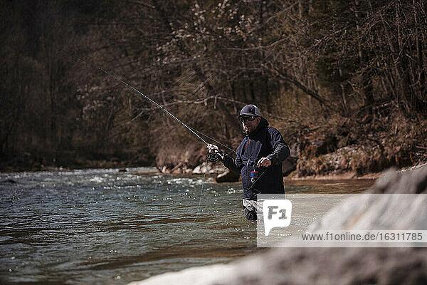 Fischer beim Angeln im fließenden Fluss im Wald