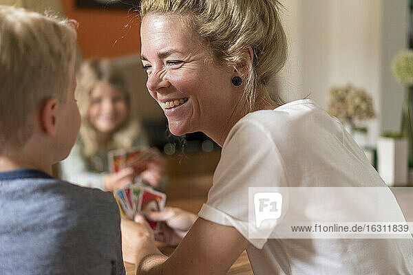 Smiling woman looking at son while playing cards