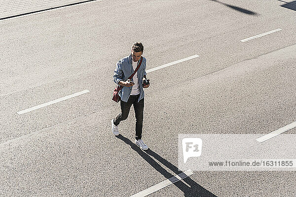 Man using mobile phone while crossing street in city
