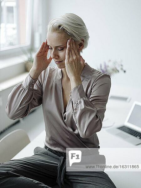 Businesswoman with head in hands meditating sitting on desk at loft office