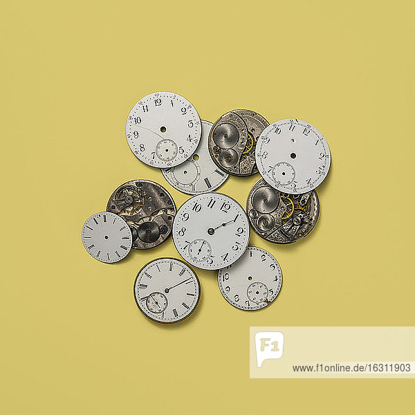 Retro watch faces and gears on yellow background