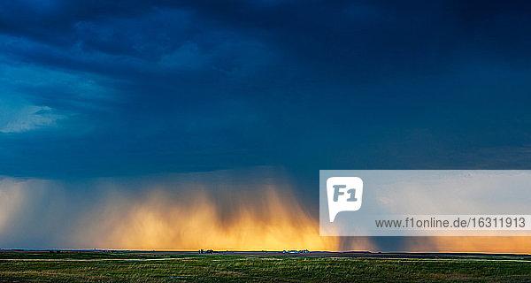 USA  South Dakota  Sun breaking through storm clouds and rain at sunset