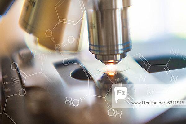 Nahaufnahme einer Labor-Mikroskoplinse mit chemischem Symbol