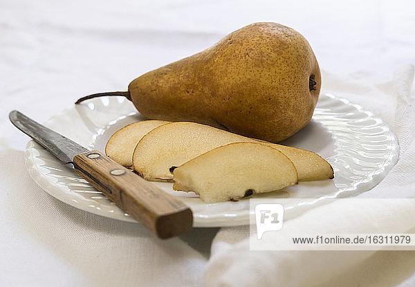Sliced pear and knife on plate