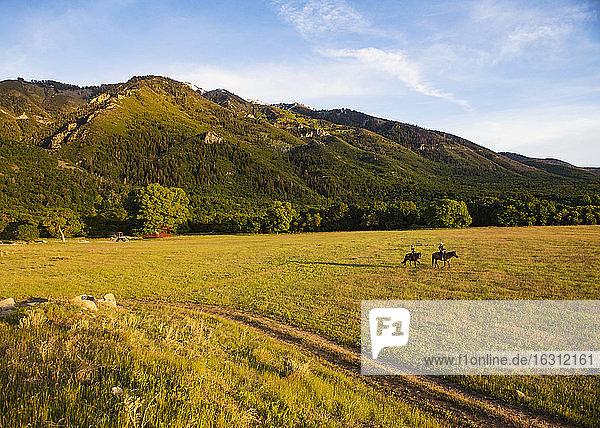 USA  Utah  Salem  Vater und Tochter (14-15) reiten Pferde bei Sonnenuntergang