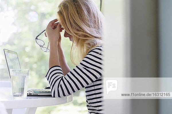 Frau  die einen Laptop benutzt und Kopfschmerzen hat