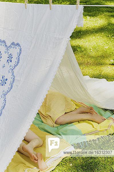 Mädchen (6-7) und Junge (4-5) entspannen sich im selbstgebauten Zelt im Hinterhof