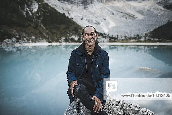 Italy  South Tyrol  Cortina d Ampezzo  lake Sorapis  Portrait of young man sitting on rock at mountain lake