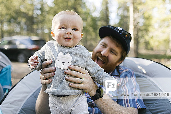 Smiling man holding baby son (6-11 months) on camping  Wasatch-Cache National Forest