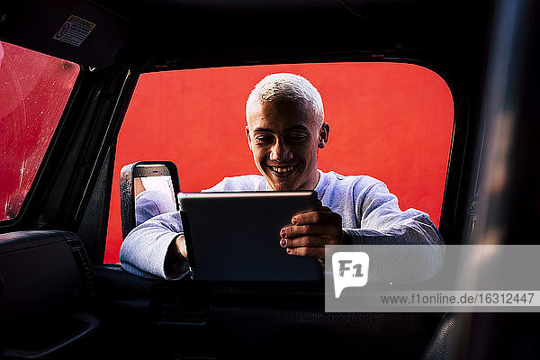 Teenager (16-17) using tablet leaning against car