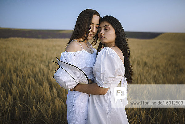 France  Women in white dresses embracing in field