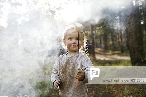 Portrait of girl (2-3) holding marshmallow near campfire in forest  Wasatch Cache National Forest
