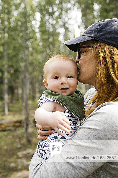 Woman kissing baby son (6-11 months) in forest  Wasatch-Cache National Forest