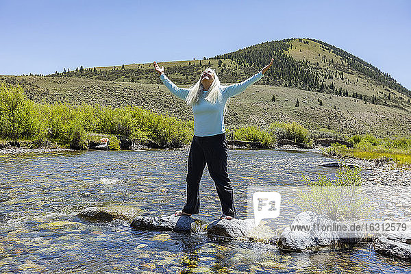 USA  Idaho  Sun Valley  Woman with arms raised standing on rocks in river