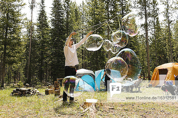 Man making large soap bubbles on camping  Wasatch-Cache National Forest