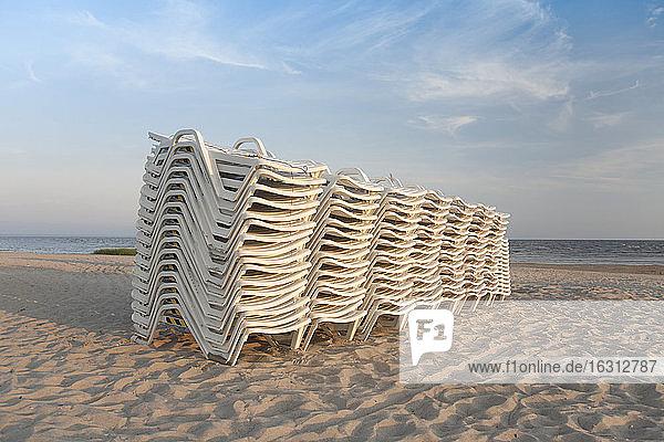 Gestapelte Liegestühle an einem Strand