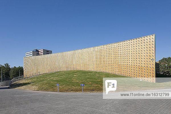 Moderne Universitätsgebäude  Holzbalken  die aus einer gebogenen Holzverkleidungswand herausragen  auf einer gekrümmten Grundfläche