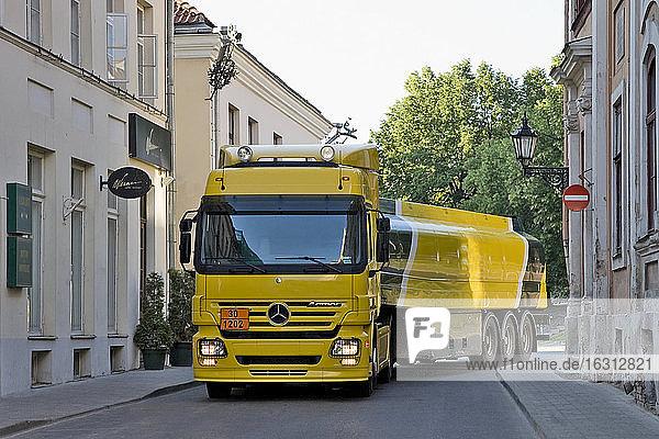 Großer gelber Lastwagen in einer engen Straße  der um eine Ecke biegt  ein Tankwagen.
