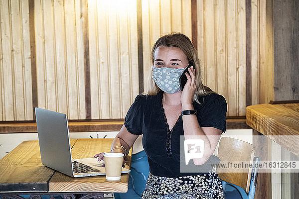 Junge blonde Frau mit blauer Gesichtsmaske  die am Tisch sitzt und ein Mobiltelefon und einen Laptop benutzt.