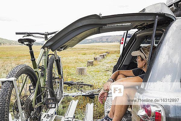 Erwachsene Frau sitzt auf der Heckklappe eines SUV und schaut auf die Aussicht