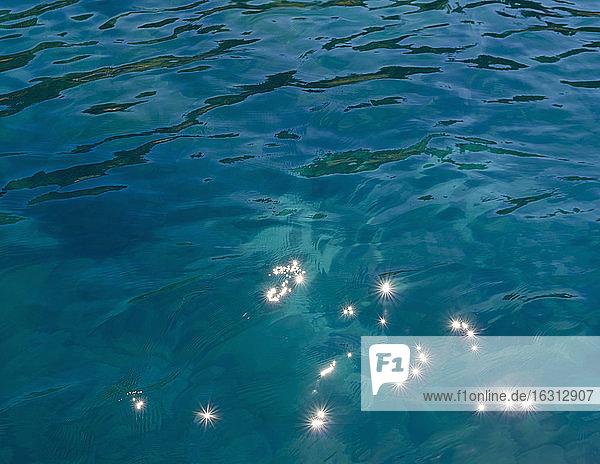 Detail des ruhigen Wassers eines Süßwassersees mit Lichtreflexionen