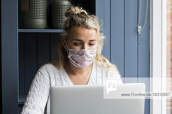 Frau mit Gesichtsmaske  die allein an einem Café-Tisch mit einem Laptop-Computer sitzt und aus der Ferne arbeitet.