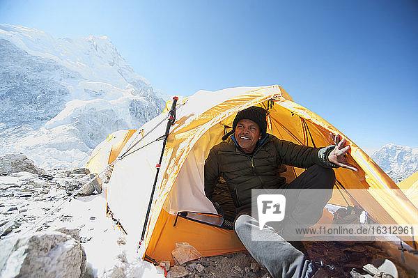 Mann sitzt im Basislagerzelt im Himalaya