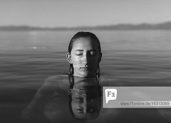 Teenager-Mädchen mit Kopf über Wasser  Augen geschlossen in ruhigem Seewasser  schwarz-weiß