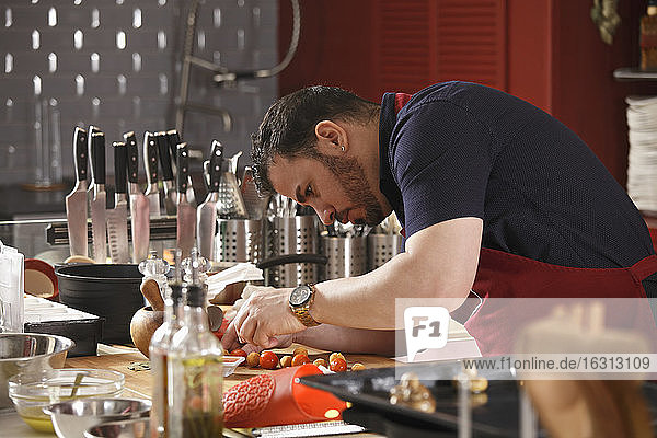 Ein Küchenchef beim Biegen und Zubereiten von Speisen in einer Großküche