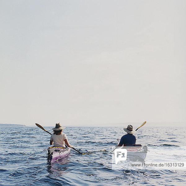 Mann und Frau mittleren Alters beim Seekajakfahren in der Abenddämmerung Mann und Frau mittleren Alters beim Seekajakfahren in der Abenddämmerung