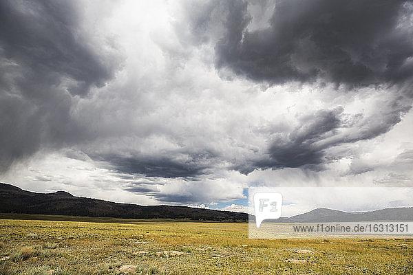 Ein stürmischer Himmel mit schweren grauen Wolken  Berge in der Ferne.